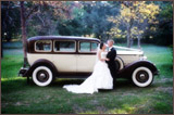 photo of a bride and groom in front of a vintage looking vehicle