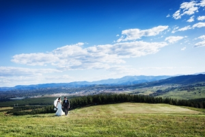 A bride and Groom Walking In Grass